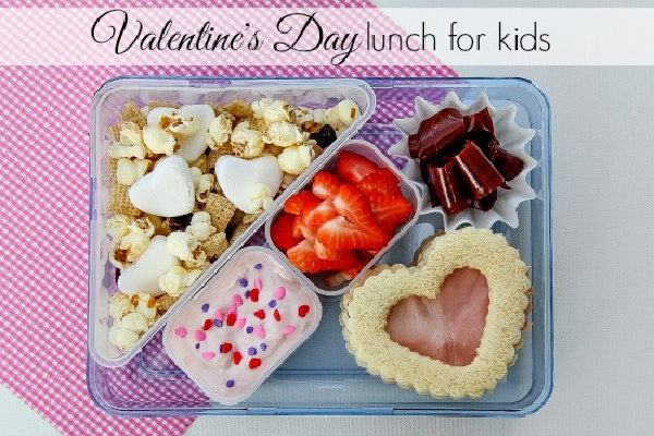 a lunchbox for kids with a heart shaped sandwich, strawberries, and other Valentine's Day treats