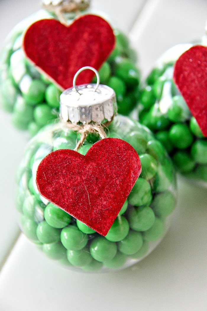 clear christmas ornaments filled with green candy and a red wood heart on the outside