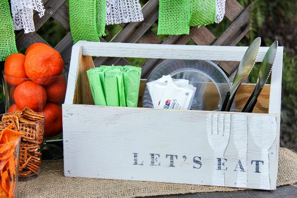 a wood crate with napkins and utensils for a party