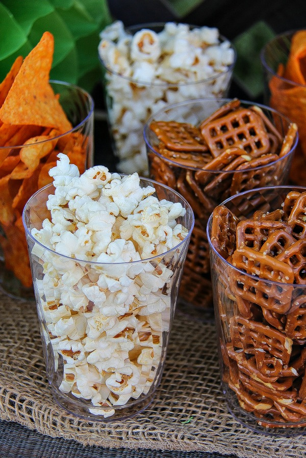 clear drinking cups filled with popcorn, pretzels, and corn chips