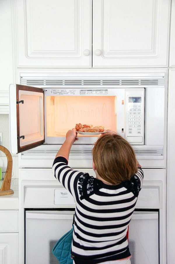 girl putting a plate of wings in the microwave