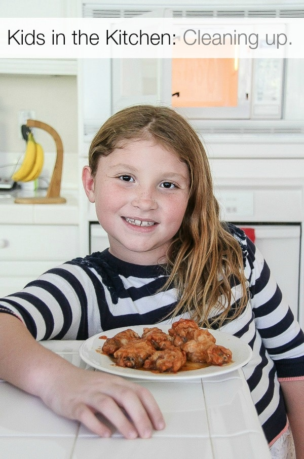 a girl standing at a kitchen counter with hot wings on a plate