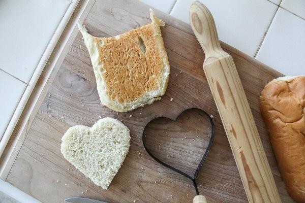 bread cut into a heart shape on a cutting board