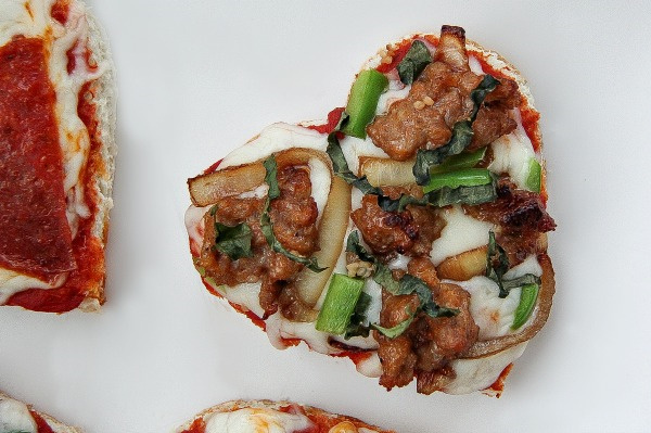 heart shaped sausage and basil pizza with caramelized onions