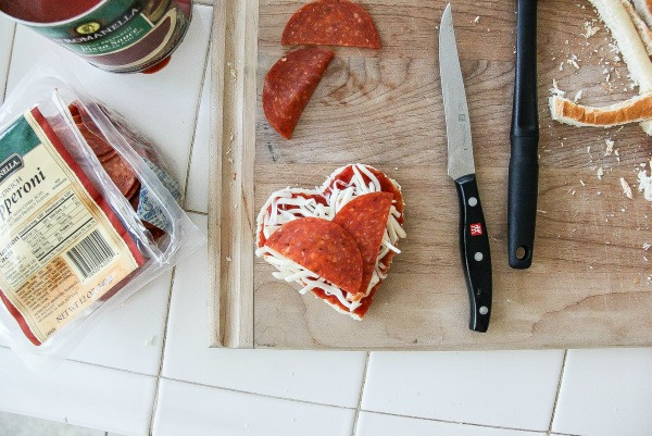 pepperoni and cheese heart shaped pizzas being made