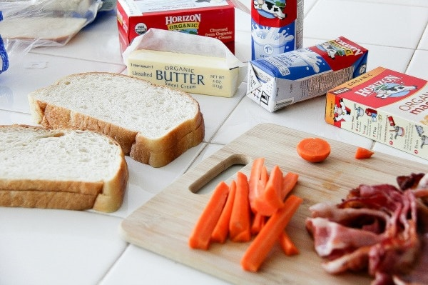 bread, carrot sticks, and bacon on a counter to make lunch