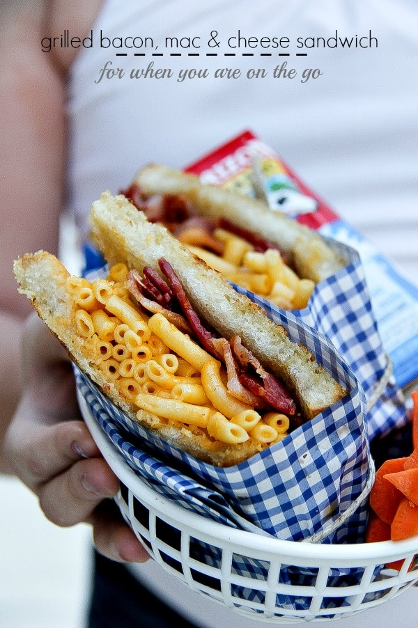 girl holding a food basket containing a bacon with mac & cheese sandwich