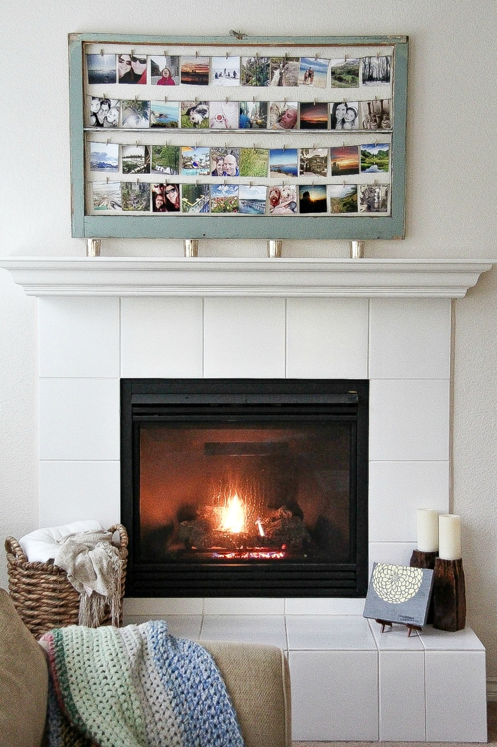 a blue frame containing square photos hanging over a fireplace