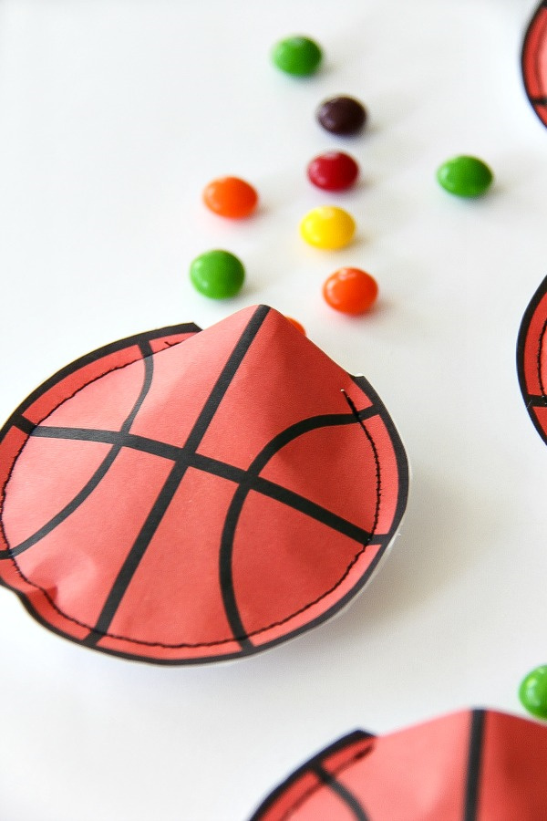 a paper basketball pouch with skittles spilling out of it