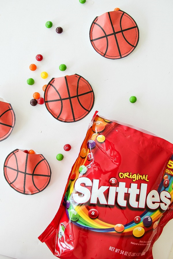 a bag of skittles with paper basketballs scattered