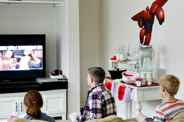 a big hero 6 movie night set up with kids watching the movie and a food table