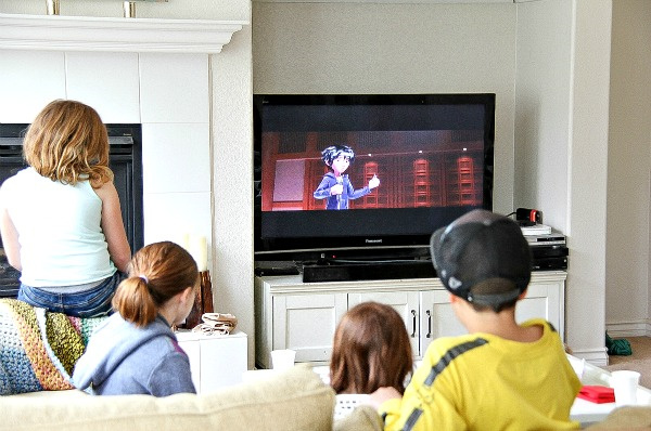 kids sitting on a couch watching big hero 6 on the television