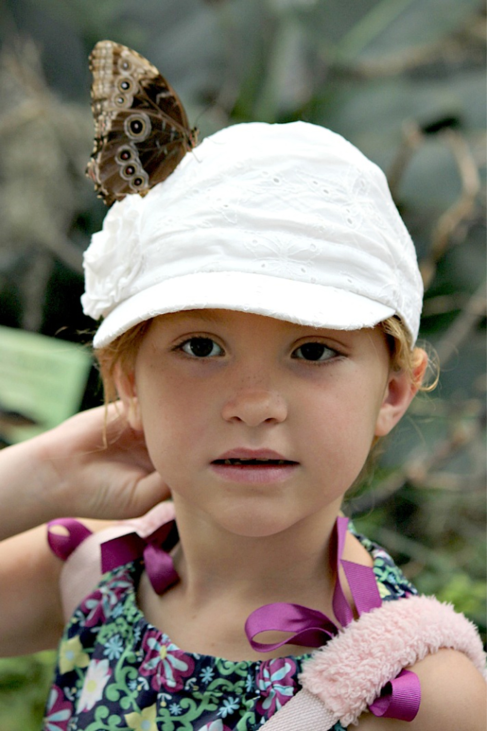 a girl with a butterfly on her hat