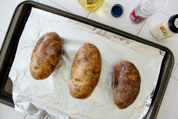 russet potatoes on a baking tray lined with parchment paper
