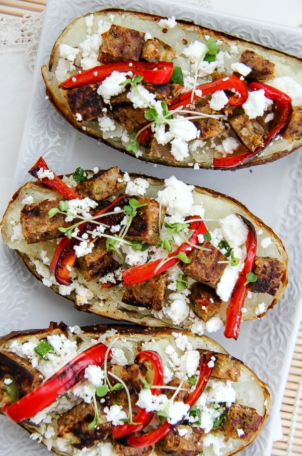 baked potatoes topped with vegetable patties, red pepper and feta cheese