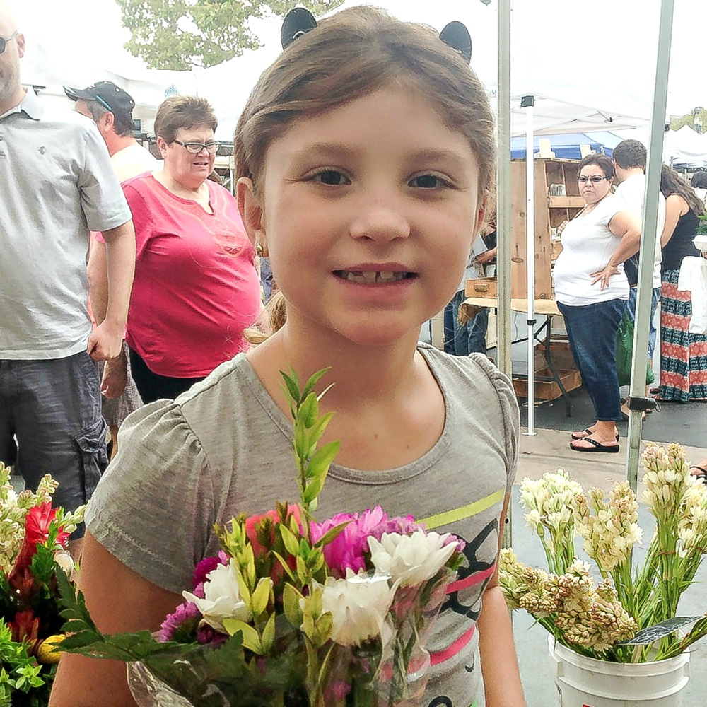 a girl buying flowers at a farmers market