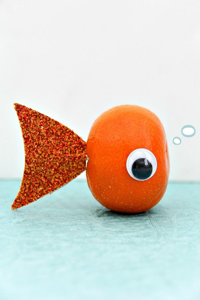 a mandarin with an eye and cardboard fish tail