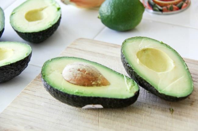 avocados cut in half on a cutting board