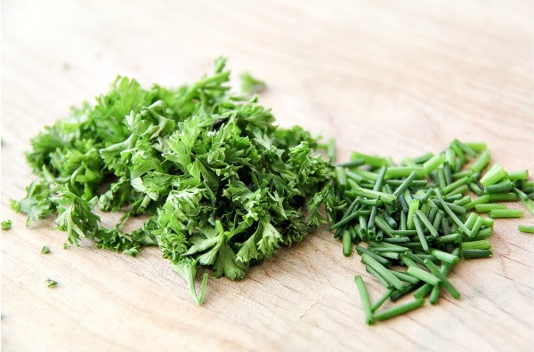 chives and parsley on a cutting board