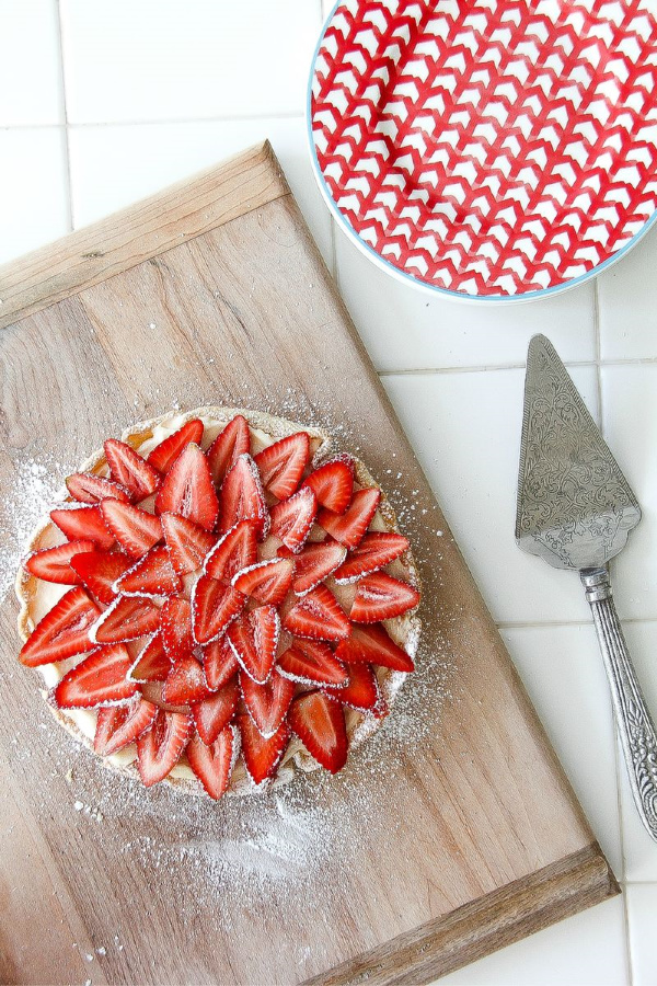 a strawberry cheesecake on a cutting board with plates