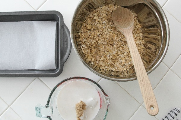 a bowl of oats, a lined baking pan, and a cup of sugar