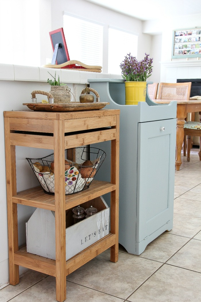 a wood storage shelf and a wood trash can cabinet inside a kitchen