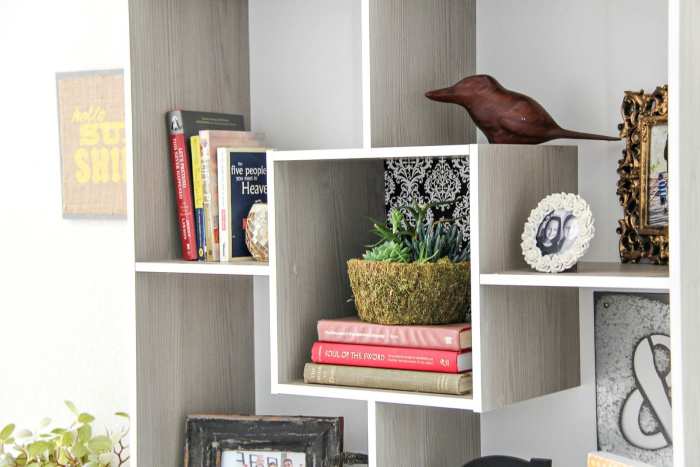 square shelving with books, frames, and a plant