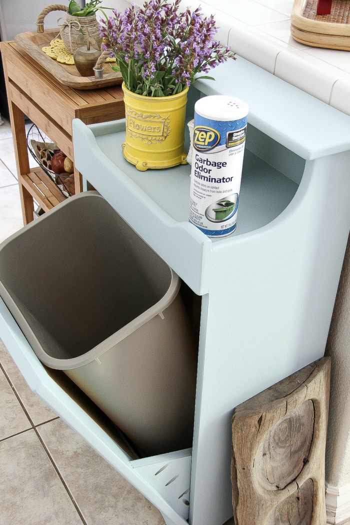 a tilt out wood trash can cabinet open with a plastic trash can inside