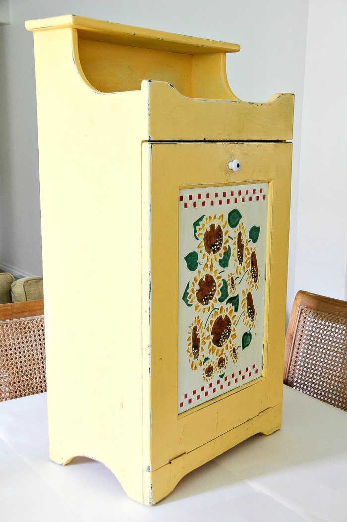 trash can cabinet painted yellow with sunflowers