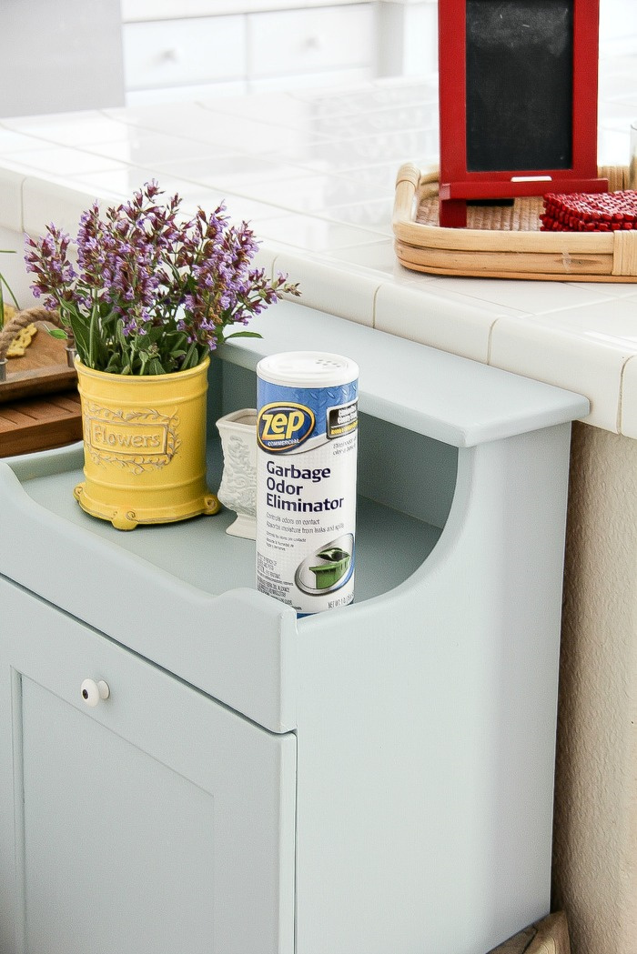 zep garbage odor eliminator on top of a wood trash can cabinet