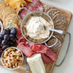a charcuterie board with nuts, meats, cheese, fruit, and spread