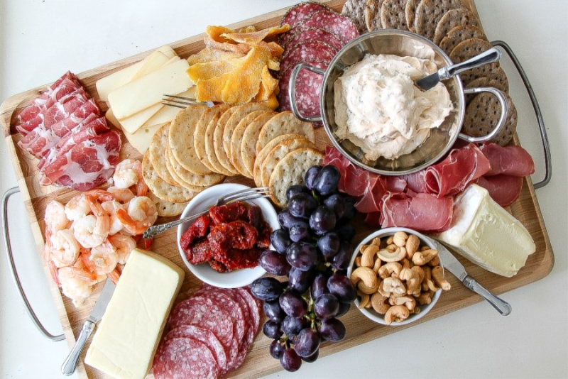 a gluten free charcuterie board with shrimp, meats, cheese, and fruit
