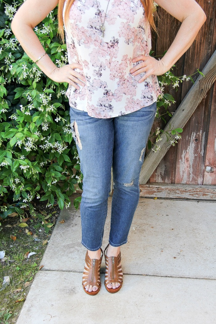 woman wearing denim jeans with brown sandals and a pastel floral top