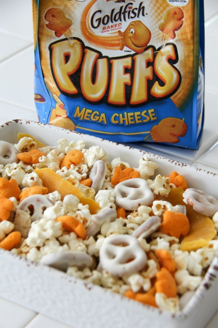 a bag of goldfish puffs behind a gluten-free snack mix in a bowl