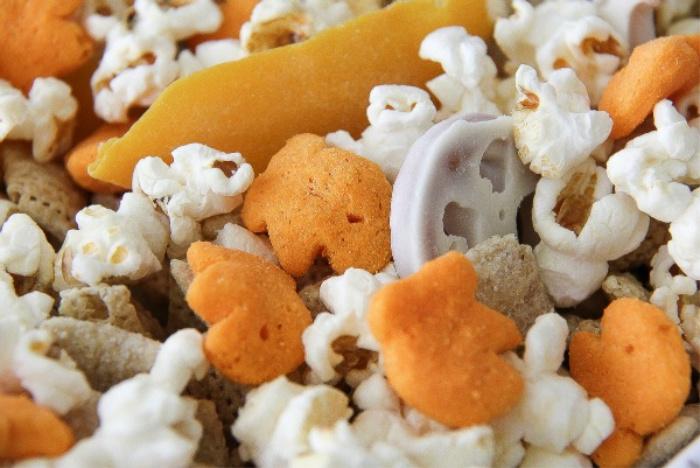 goldfish puffs, popcorn and yogurt covered pretzels in a bowl