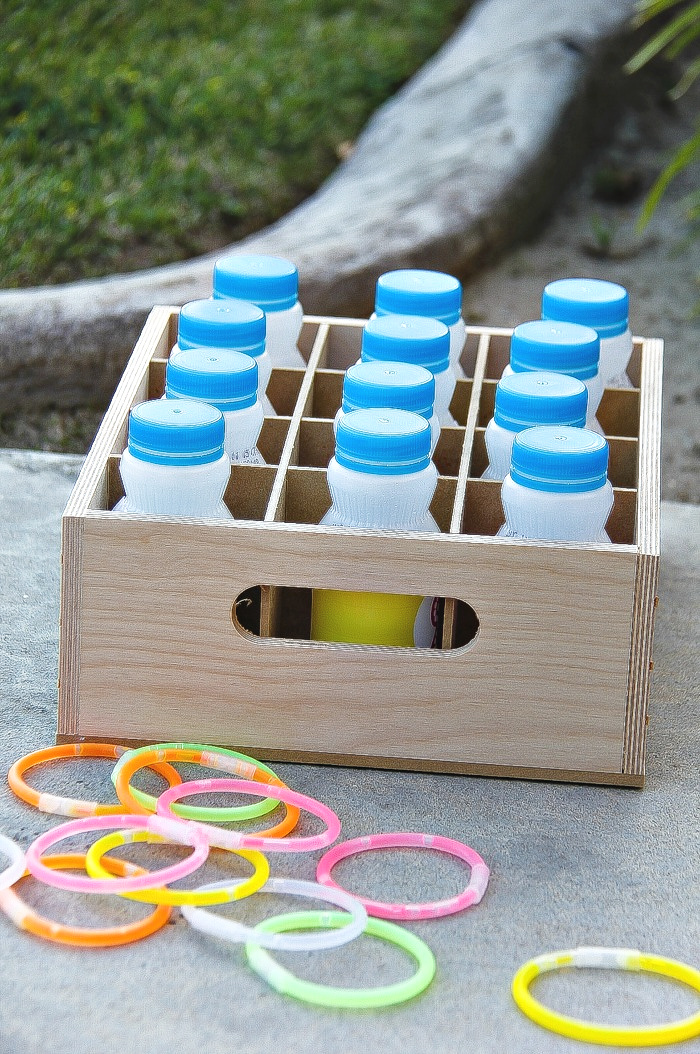 a ring toss game made out of drink bottles and old glow in the dark bracelets
