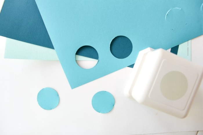 a hole punch with blue circles cut out of card stock