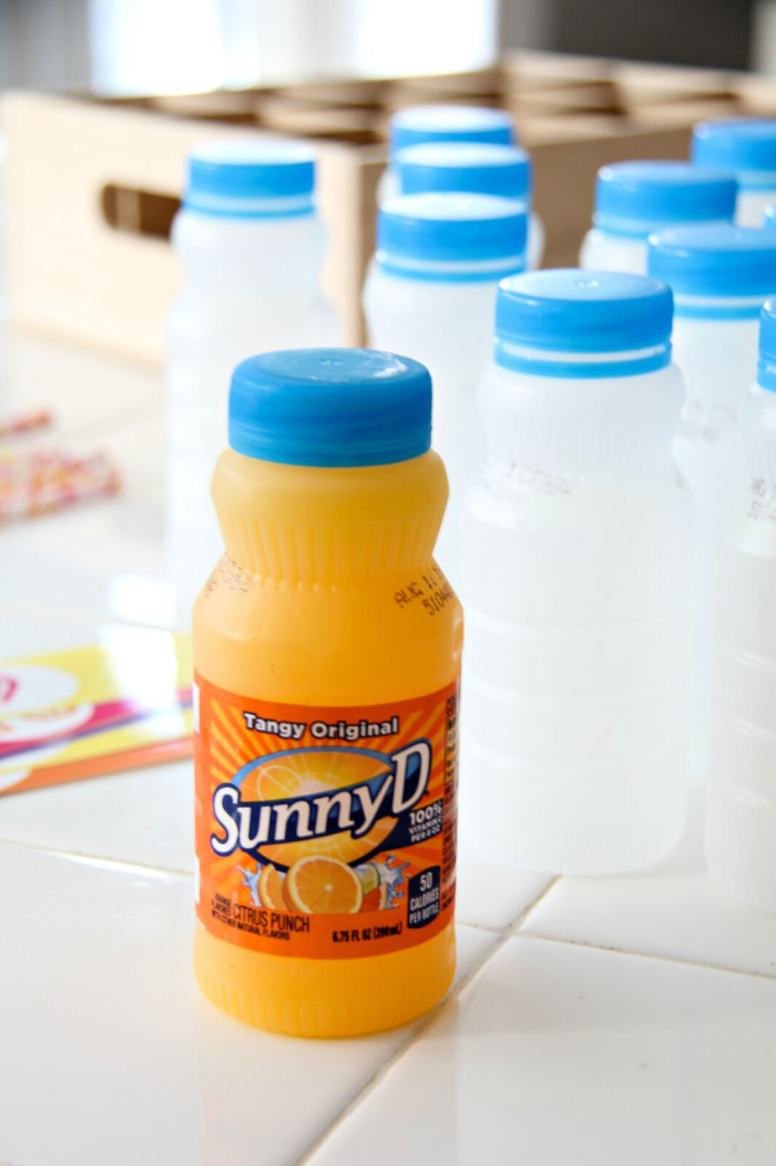 a bottle of SunnyD with more empty bottles with the labels removed