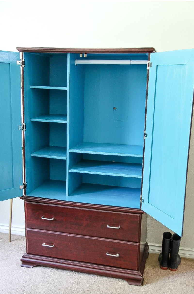 a dark wood armoire painted bright blue inside