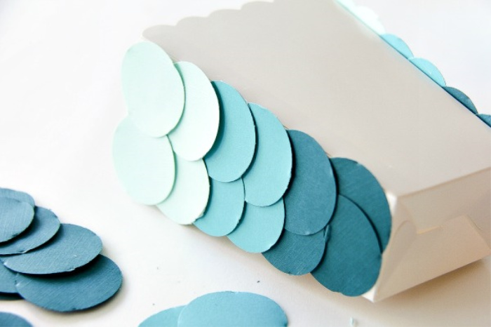 blue ombre circles being attached to a cardboard snack tub