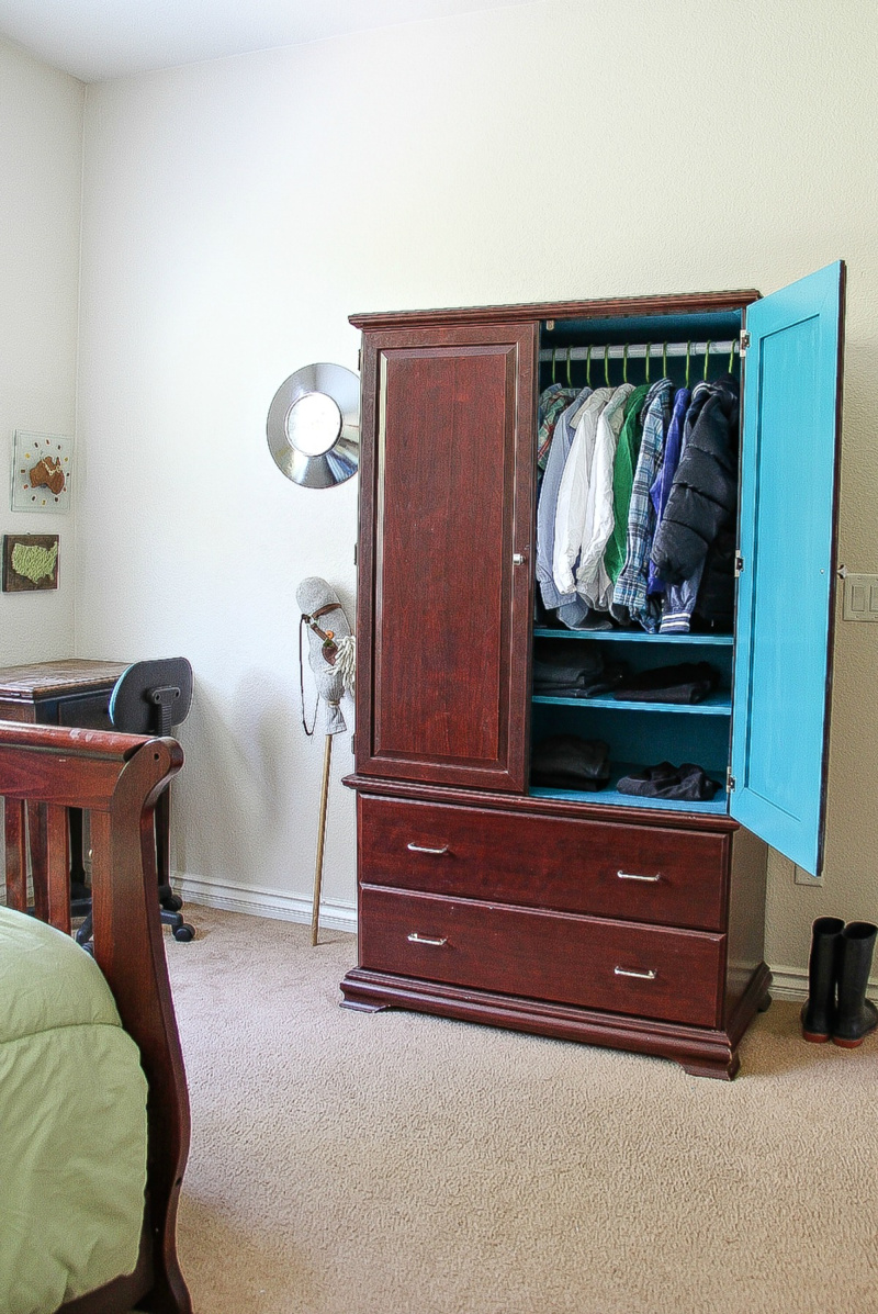 a dark wood armoire in a boys bedroom