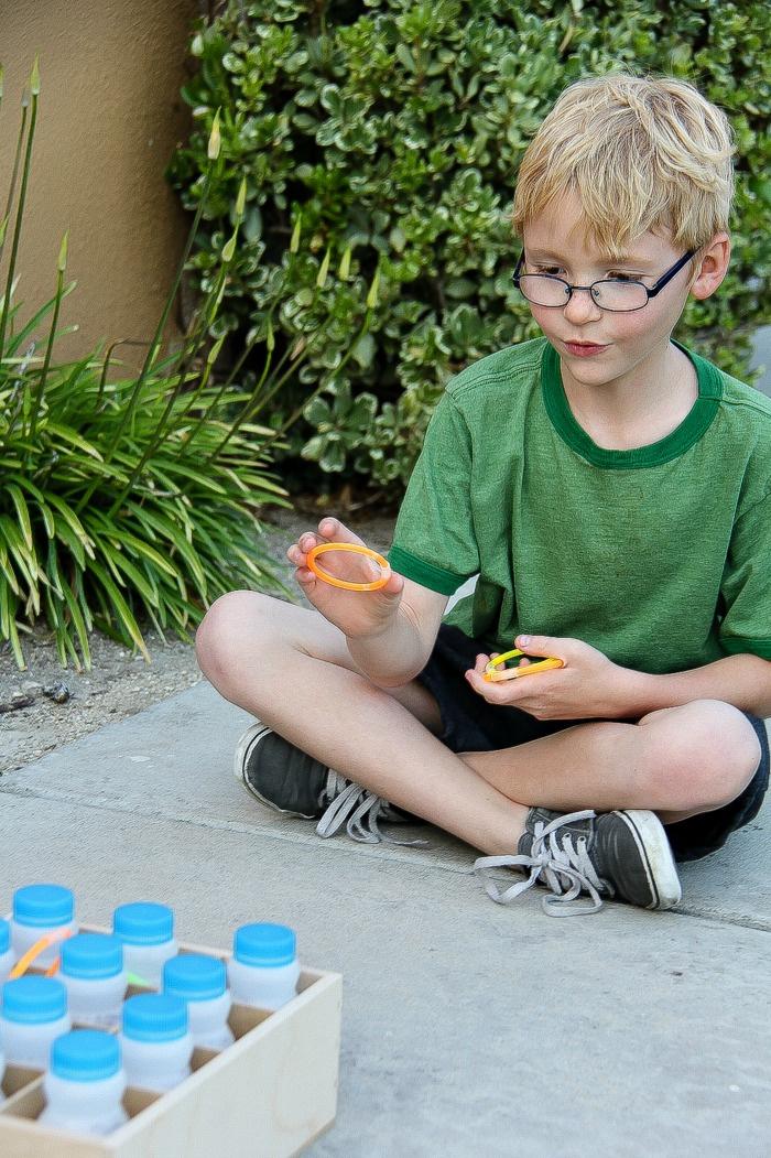 a boy playing a handmade ring toss game