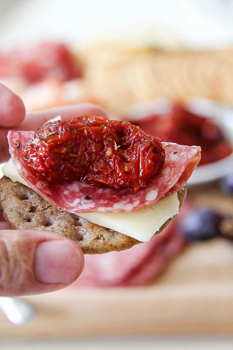 sundried tomato with salami and cheese on a cracker