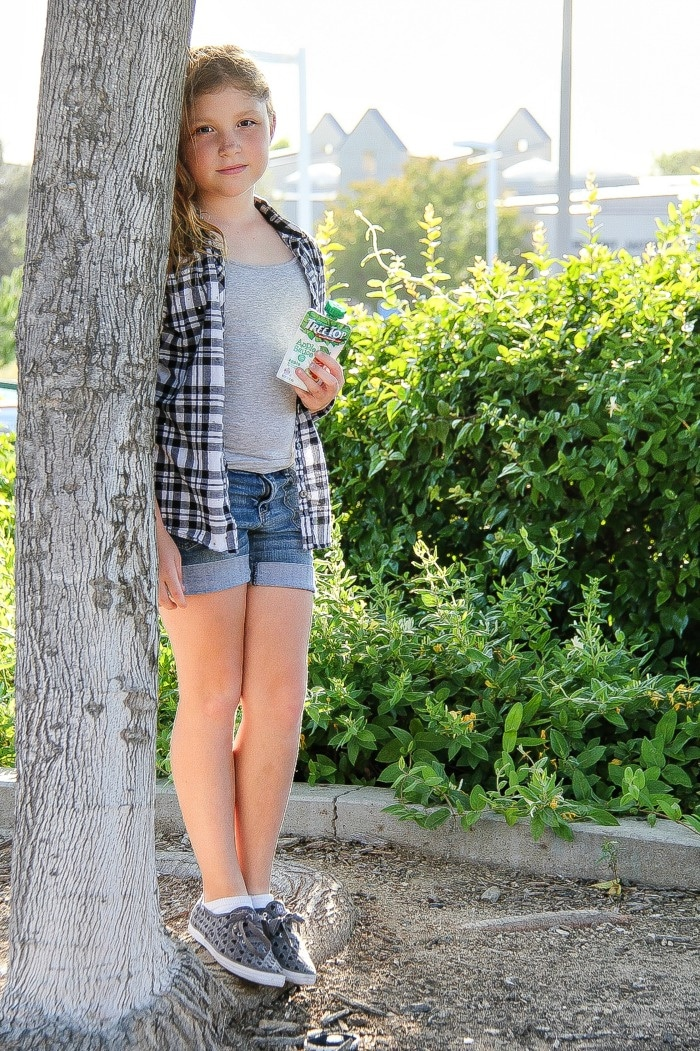 girl wearing shorts and a checked shirt at the park