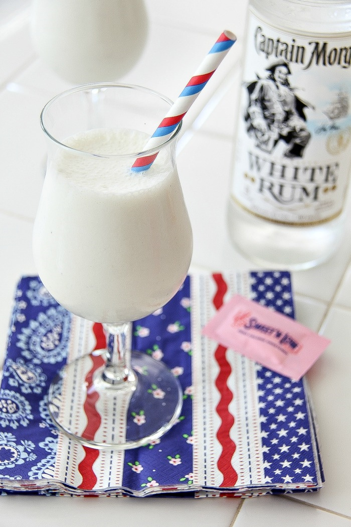 a white milkshake in a glass with a bottle of white rum