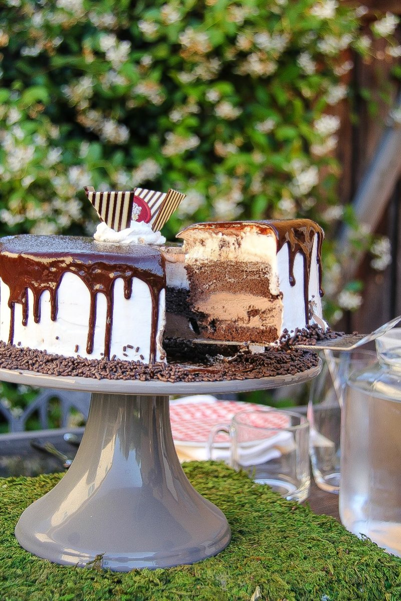 an ice cream cake on a cake stand with a slice of cake being removed
