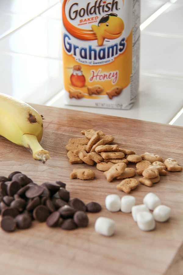 honey graham goldfish crackers with chocolate chips, marshmallows and a banana