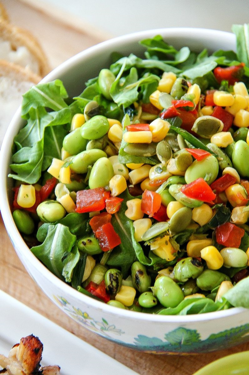 salad in a bowl with greens, edamame, red bell pepper and corn