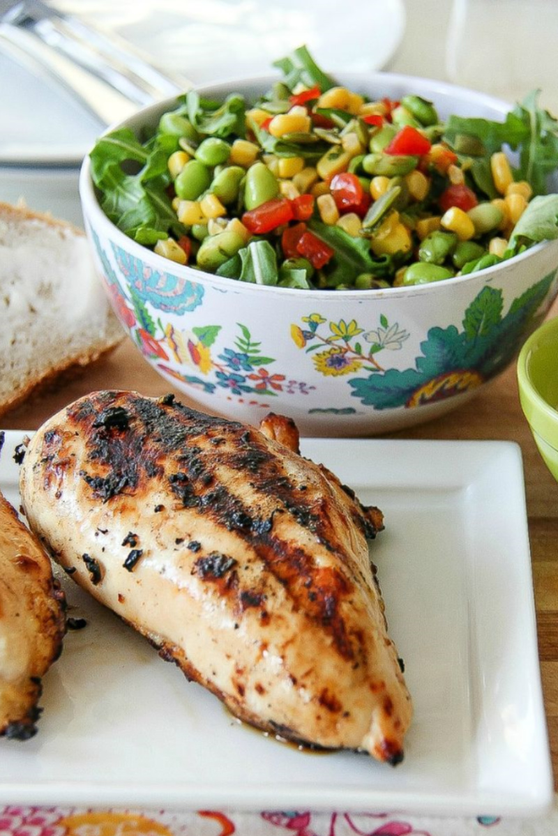 grilled chicken with a bowl of salad behind it
