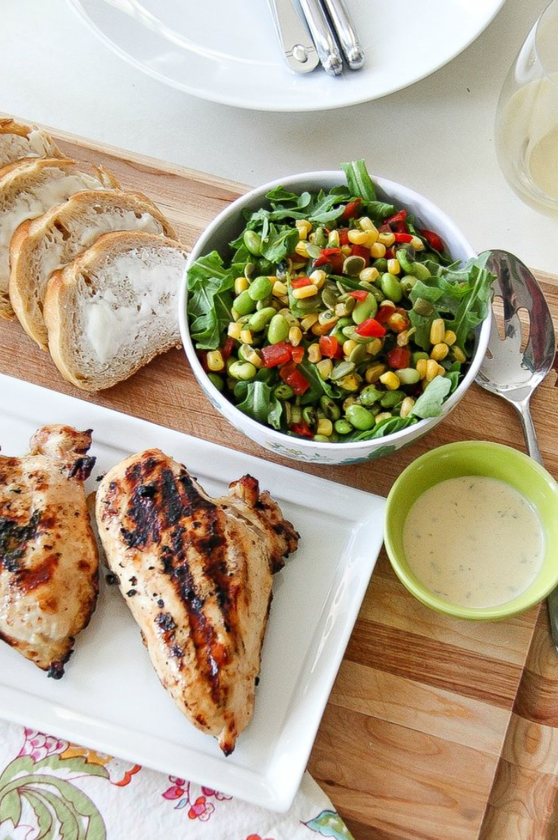 grilled chicken on a serving tray with a side salad and buttered bread